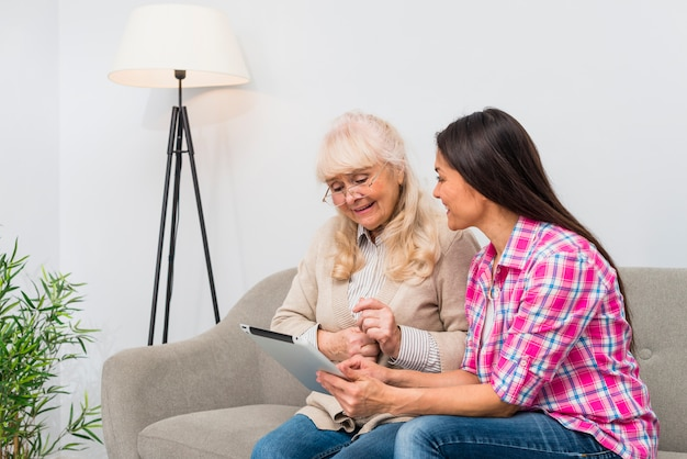 Silly senior mother and her daughter using a digital tablet while sitting on sofa