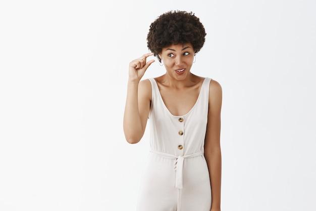 Глупая стильная девушка позирует у белой стены