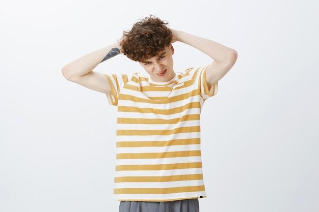Ragazzo adolescente sciocco in posa contro il muro bianco