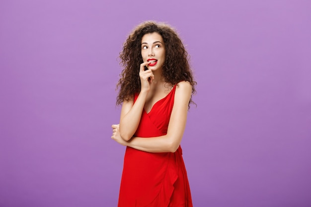 Silly and timid charming woman with dark curly hair in stylish evening dress with red lipstick biting finger looking cute at upper right corner thoughtful imaging or dreaming about desirable thing.