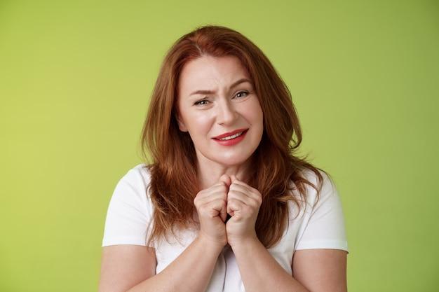 愚かな感触の優しい赤毛魅力的な中年女性ため息をつく喜んで見つめる賞賛喜んでプレス手を一緒に心温まる魅惑的な表情感謝する素敵なカメラの緑の壁