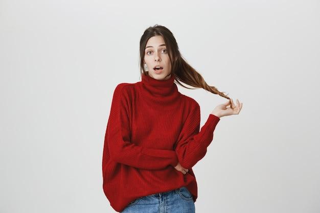 Глупая беззаботная молодая женщина играет с волосами, разговаривает