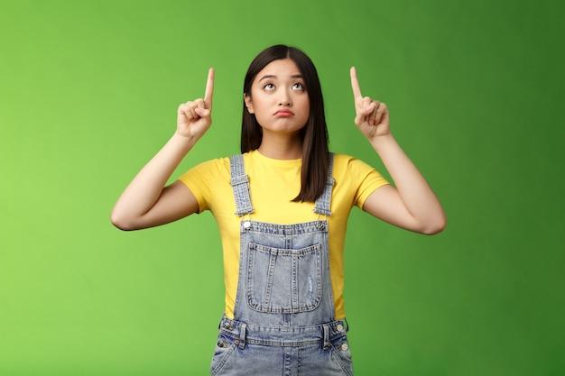 어리석은 화난 귀여운 아시아 소녀는 슬프고 우울한 위쪽을 바라보고, 불쾌한 얼굴을 하고, 새로운 제품을 꿈꾸며, 돈을 들이지 않은 것을 후회하고, 녹색 배경에 서 있습니다.