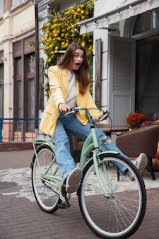 Глупая женщина, едущая на велосипеде на открытом воздухе в городе