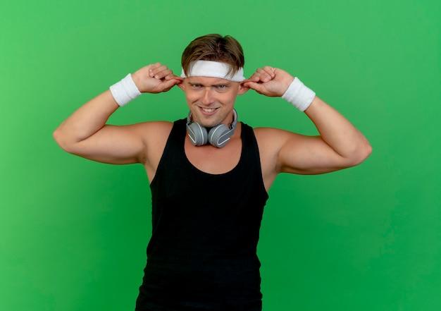 녹색 벽에 고립 된 원숭이 귀를 만드는 목에 헤드폰으로 머리띠와 팔찌를 착용하는 어리석은 젊은 잘 생긴 스포티 한 남자