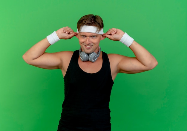 Silly young handsome sporty man wearing headband and wristbands with headphones on neck making monkey ears isolated on green wall