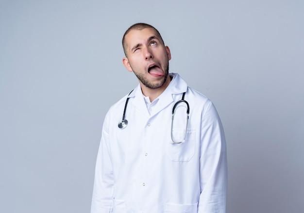 Sciocco giovane medico maschio che indossa veste medica e stetoscopio intorno al collo alzando lo sguardo e mostrando la lingua con un occhio chiuso isolato sul muro bianco