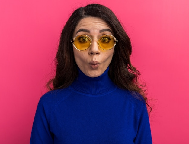 Stupida giovane donna graziosa che indossa occhiali da sole guardando la parte anteriore che fa la faccia di pesce isolata sulla parete rosa
