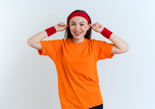 Silly young sporty woman wearing headband and wristbands smiling looking making big ears isolated