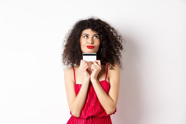 ロマンチックに見え、プラスチックのクレジットカードを保持し、白い背景の上に立って買い物を考えている愚かな若い女性。コピースペース