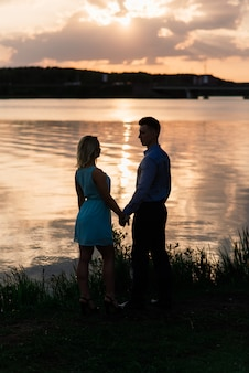 Silouette, loving couple on the lake during sunset. golden hour