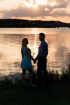 日没時に湖でカップルを愛するシルエット。ゴールデンアワー