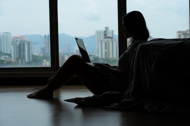 ラップトップに取り組んでコーヒーを飲みながら、高層階からの美しい景色を一望できるパノラマの窓際のベッドの近くの床に座っているsiluet女の子。スタイリッシュでモダンなインテリア。居心地の良い職場