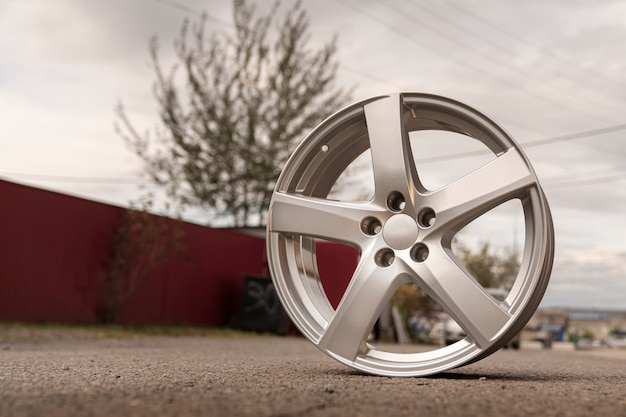 Silver aluminum alloy wheel outdoor under the open sky.