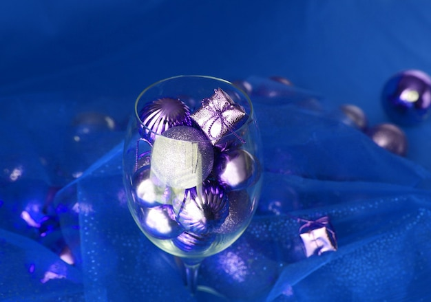 은색과 파란색 크리스마스 배경에는 포도나무 유리와 금색 크리스마스 장식이 있습니다. 크리스마스 장식이 있는 덩굴 유리