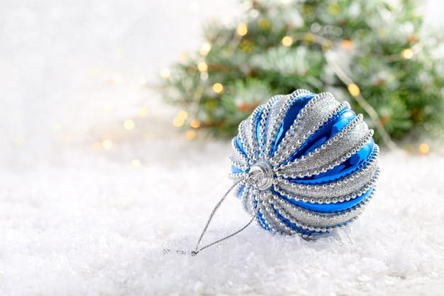 Серебряный и синий новогодний шар на заснеженном столе