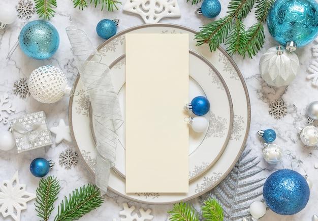 Серебряная и синяя праздничная сервировка стола с украшениями и еловыми ветками с пустой картой
