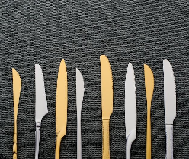 어두운 배경에 은색과 금색 칼. 은식기, 주방 용품