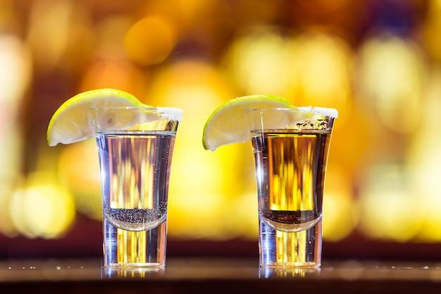 明るいライトのガラスの銀と金のテキーラ。伝統的なメキシコの飲み物。
