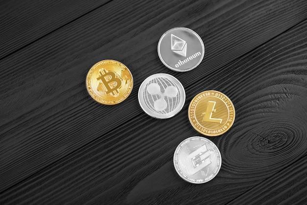 나무 배경에 bitcoin, 리플 및 ethereum 기호로 은색과 황금 동전.