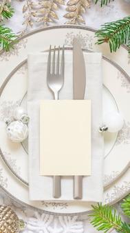 Серебряная и золотая сервировка праздничного стола с украшениями и еловыми ветками с пустой картой