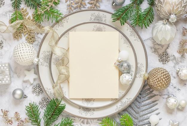 Серебряная и золотая сервировка праздничного стола с украшениями еловых веток и видом сверху карты