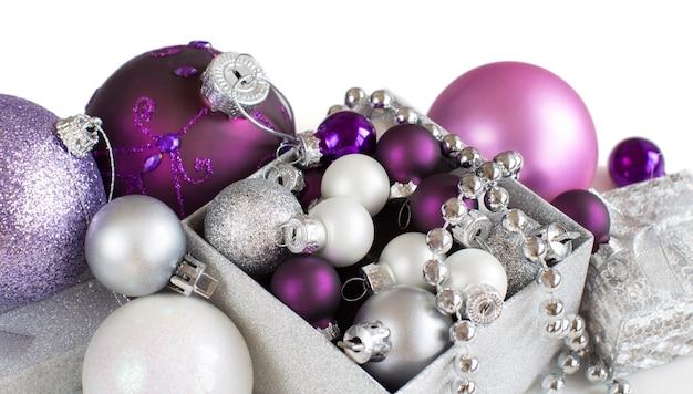 Серебряные и фиолетовые рождественские украшения граничат на белом крупным планом