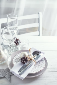 Серебряный и белый рождественский стол с рождественскими украшениями над светлым окном