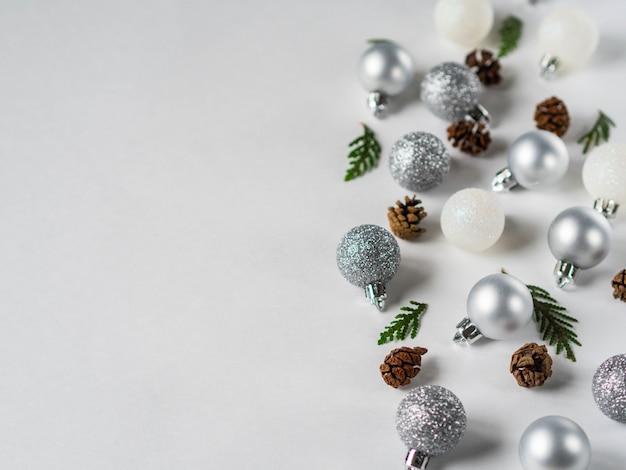 銀と白のグリッタークリスマスボール、コーン、クリスマスツリーブランチ国境フラットレイアウト。コピースペース