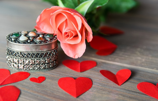 Silver antik casket with flower and red paper hearts.