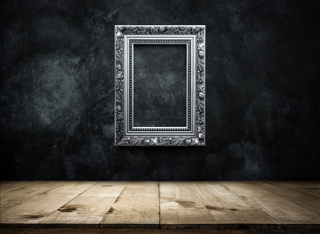 Silver antique photo frame on dark grunge wall background with wooden table top