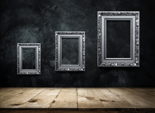 Silver antique picture frame on dark grunge wall with wooden table top