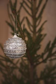 Серебряный шар, усыпанный конфетти, на вечнозеленой елке