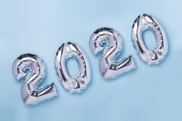 Silver balloons in the form of numbers 2020 on blue