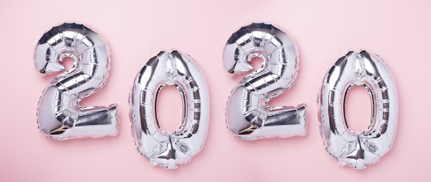Silver balloons in the form of numbers 2020 on pink