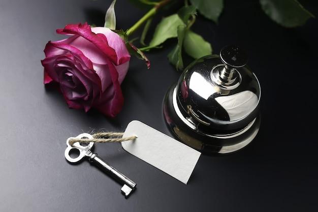 銀の鐘と黒い背景のホテルのレセプションの鍵