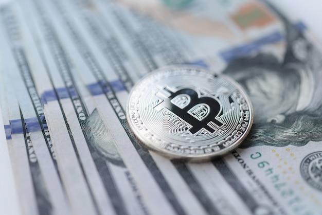 Серебряная монета биткойн, лежащая на куче долларовых купюр крупным планом