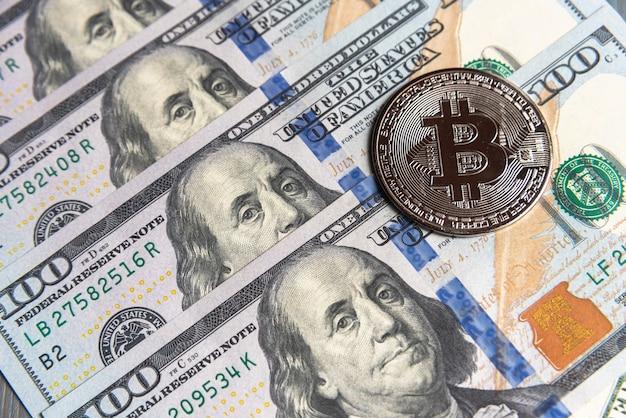 Серебряная криптовалюта биткойн на доллары сша. крупный план цифровой криптовалюты. обмен, бизнес, торговля. прибыль от майнинга криптовалюты. майнер с долларами и серебряной монетой биткойн.