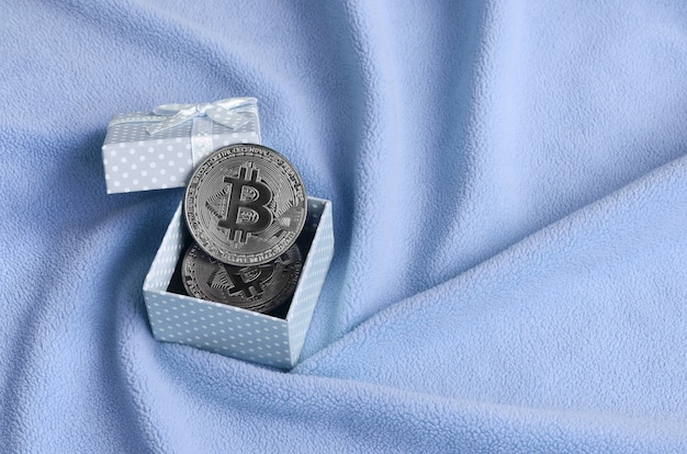 The silver bitcoin lies in a small blue gift box with a small bow on a blanket of blue fleece