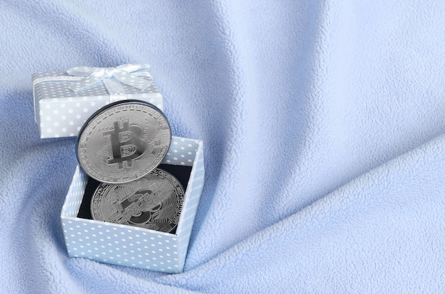 The silver bitcoin lies in a small blue gift box with a small bow on a blanket made of soft