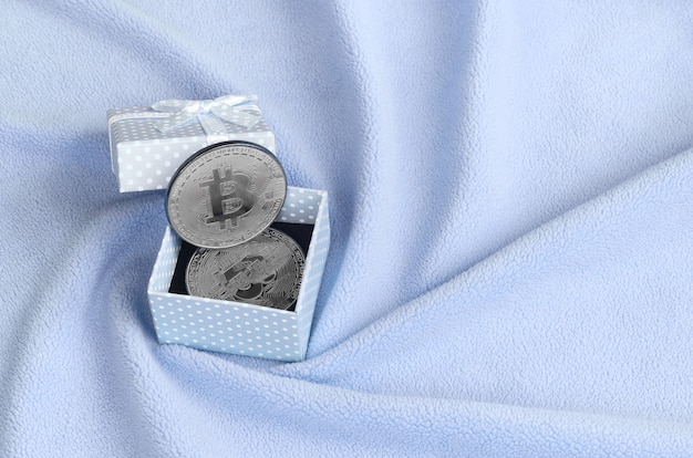 The silver bitcoin lies in a small blue gift box with a small bow