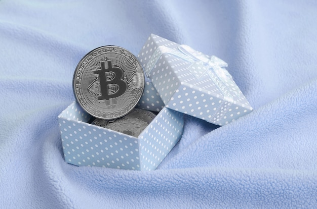 The silver bitcoin lies in a small blue gift box