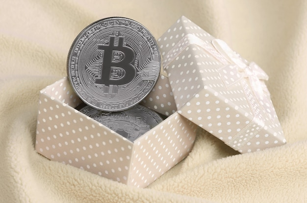 The silver bitcoin lies in a small orange gift box with a small bow on blanket