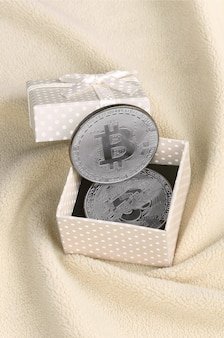 The silver bitcoin lies in a small orange gift box with a small bow
