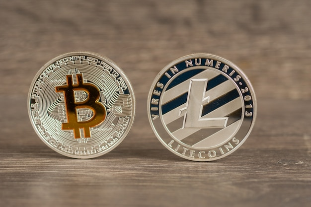 Silver bitcoin and litecoin mettallic coins on wooden table