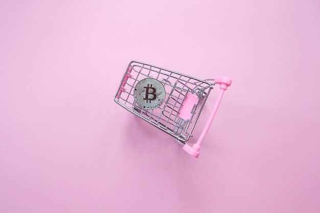 Silver bitcoin in shopping cart on a millennial pink background. top view. minimalism.