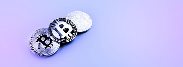 Серебряные монеты bitcoins на фиолетовой поверхности