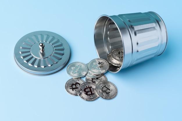 파란색 배경에 있는 쓰레기통에서 나오는 은색 비트코인. 암호화폐와 돈.