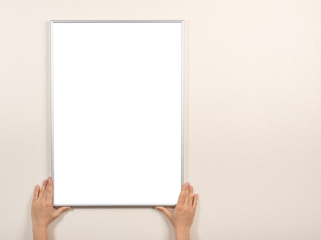 Silver blank picture frame hanging on a beige wall. hands hold photo frame  on wall.