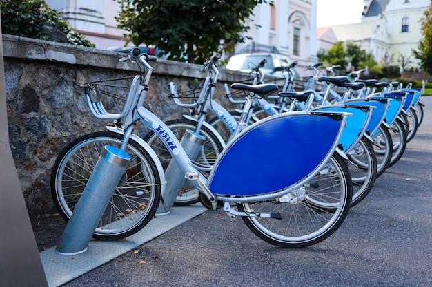 Серебристо-синий велосипед на стоянке, прокат велосипедов